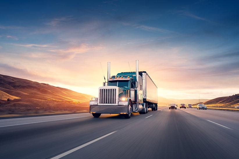 American style truck on freeway pulling load. Transportation theme. Road cars theme..jpg