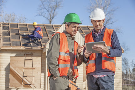 Construction workers reviews plans on tablet