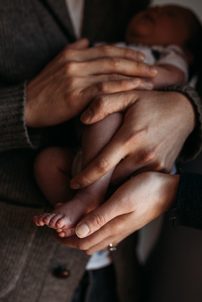 portrait of hands holding a newborn baby