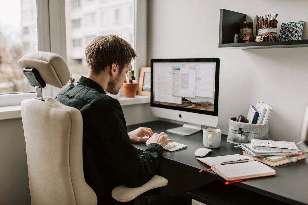 Man sitting in desk chair in front of computer looking at keyboard