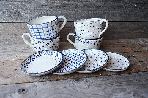 Tazze da tè bianche con decorazioni blu e piattino