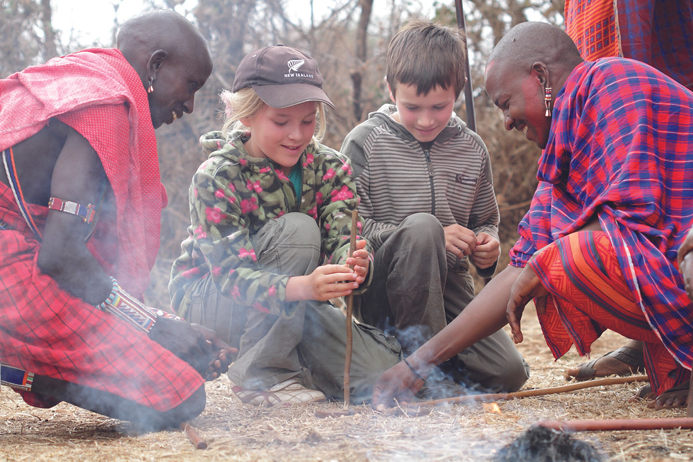 Children on safari with Maasai, learning how to make fire