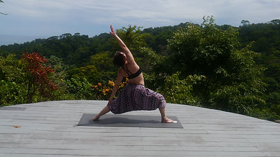 Woman in colorful yoga pants stretching on porch overlooking lush green forest