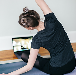 Woman sitting cross-legged stretching right arm up in front of laptop