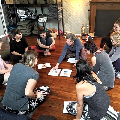 People sitting in a circle with Tara teaching hatha yoga
