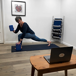 Woman stretching with yoga blocks in front of laptop