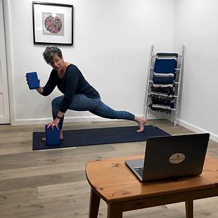 Tara with yoga blocks demostrating yoga pose on camera
