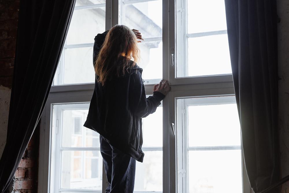 Frau steht am Fenster, schaut nach draußen, schwarze Vorhänge