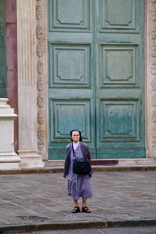 Tiny nun, giant green door. Florence, Italy.