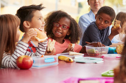 Young school kids eating lunch talking a