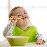 Happy infant baby boy spoon eats itself.