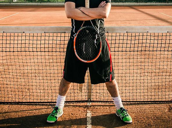 Bildausschnitt eines Tennisspielers der vor dem Tennisnetz steht und einen Tennisschläger in der Hand hält