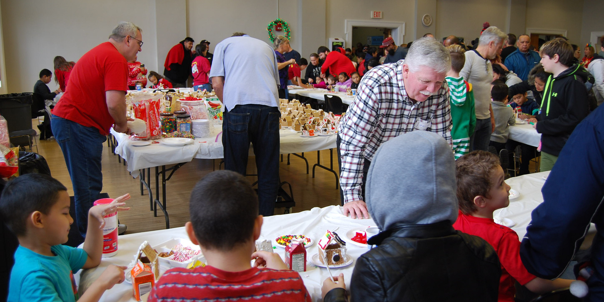Volunteers helping the children create their gingerbread houses!