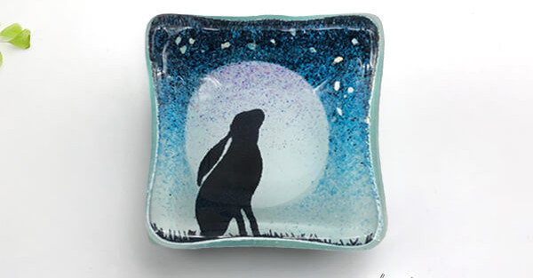 Colette Halstead glass earring dish with hare design on blue background