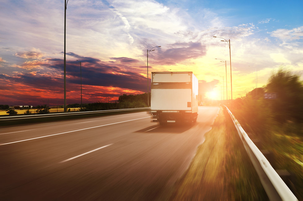 White box truck driving fast on the countryside road against night sky with beautiful suns