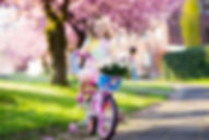 Child riding a bike on a street with blo