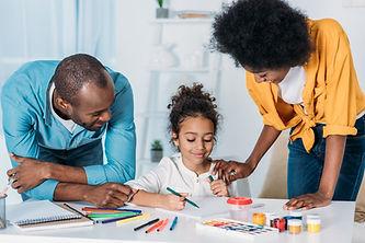 Parents helping a child paint