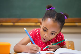 Child writing in a classroom