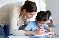 Teacher helps a student write