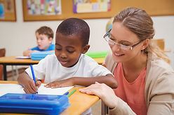 Teacher watches a student write in a classroom