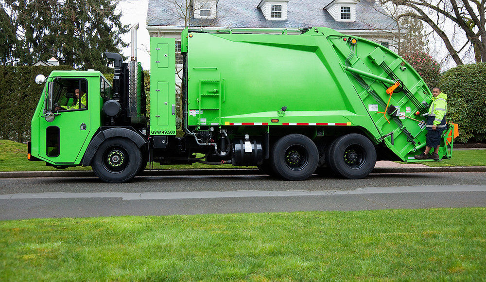 Green dumpster truck