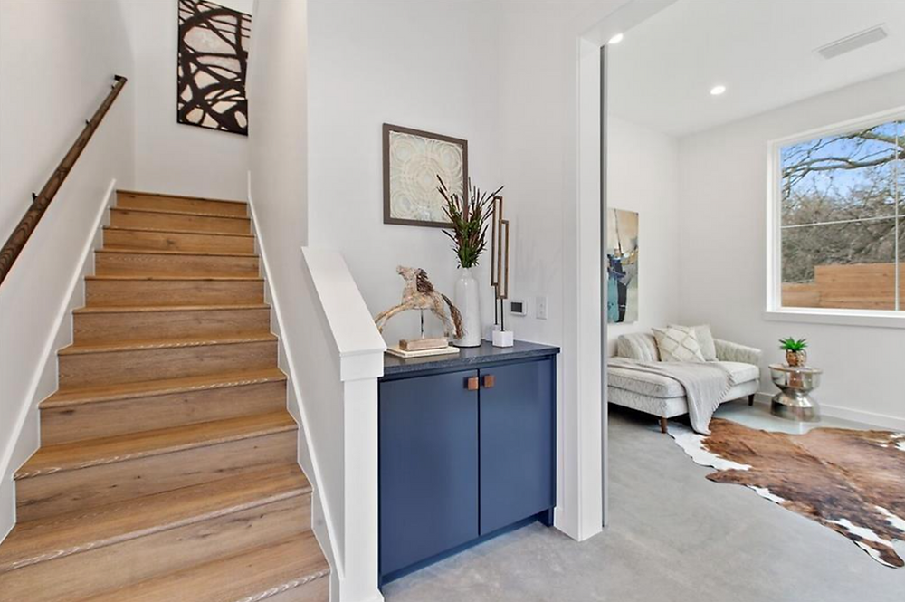 A staged home entry way. On the left, a medium-toned wood staircase. In the center, a small blue built in cabinet with modern decor. On the right, a view into the living room with a small white couch and a brown and white cow skin rug