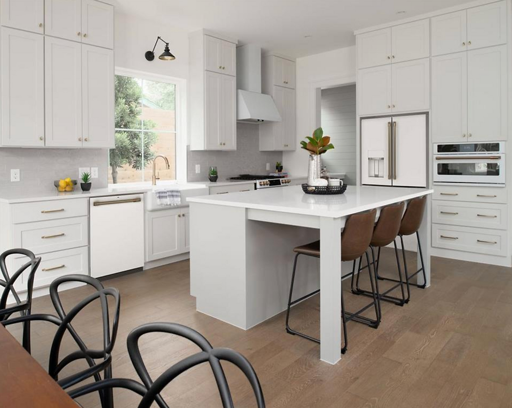 A simply staged white kitchen with modern appliances