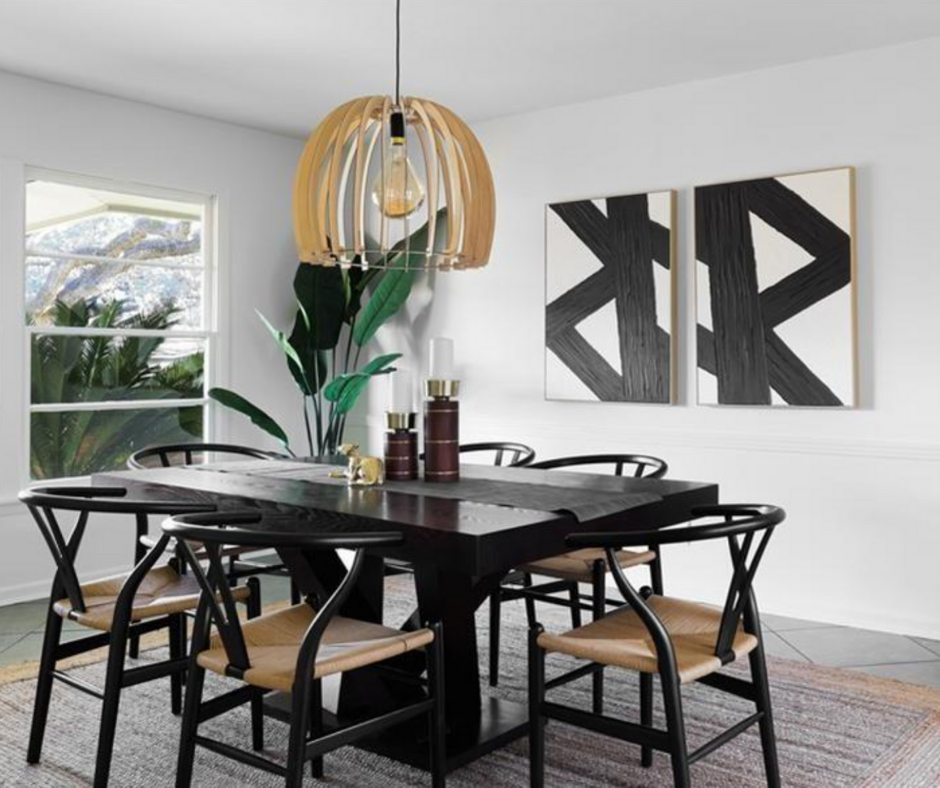 A staged modern dining room with clean white walls, and neutral rug, black table, black chairs, and wood statement chandelier