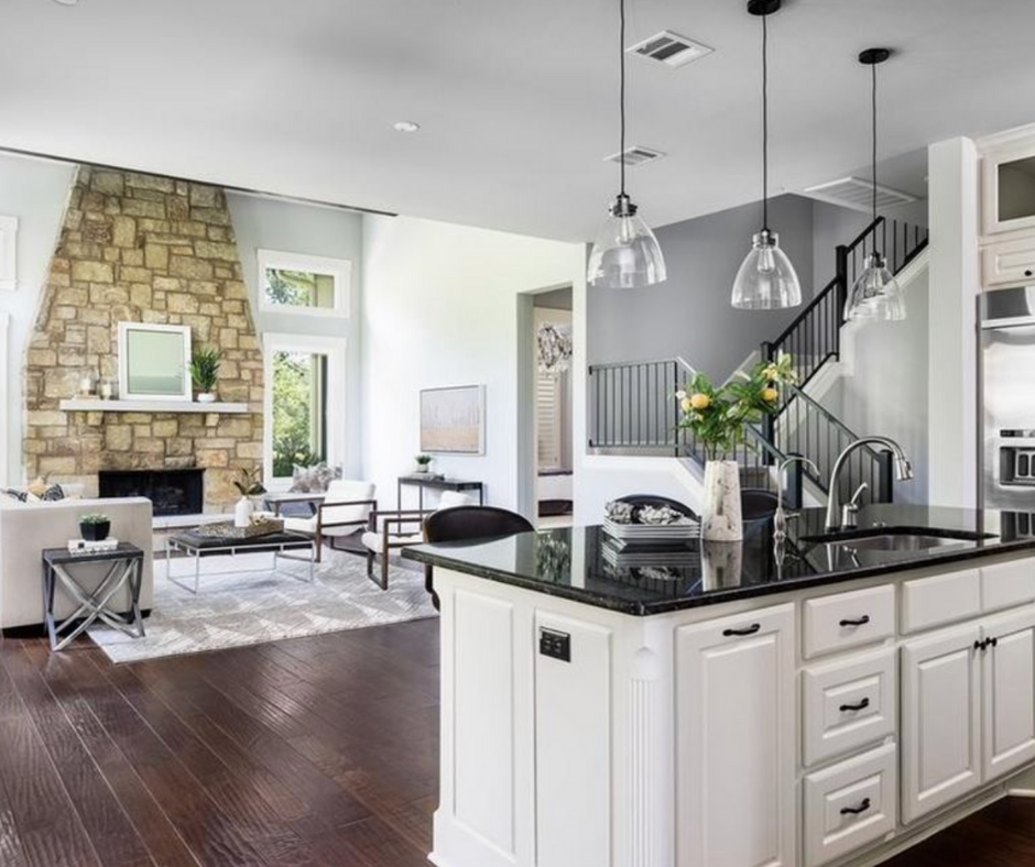 Open concept living room and kitchen with grand rock fireplace staged with modern pieces