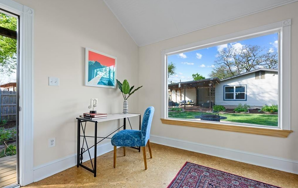 A staged home office setup in a house. A white desk with a blue chair next to a large window