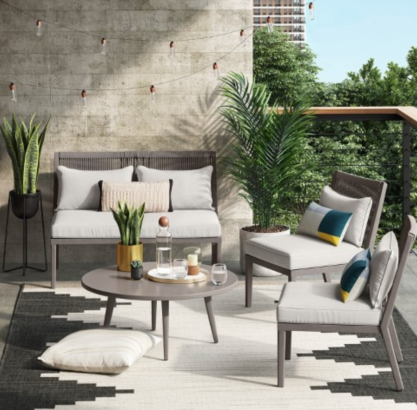 Staged patio furniture set up for a summer day. Gray wicker seating with white cushions and pillows, surrounded by plants.