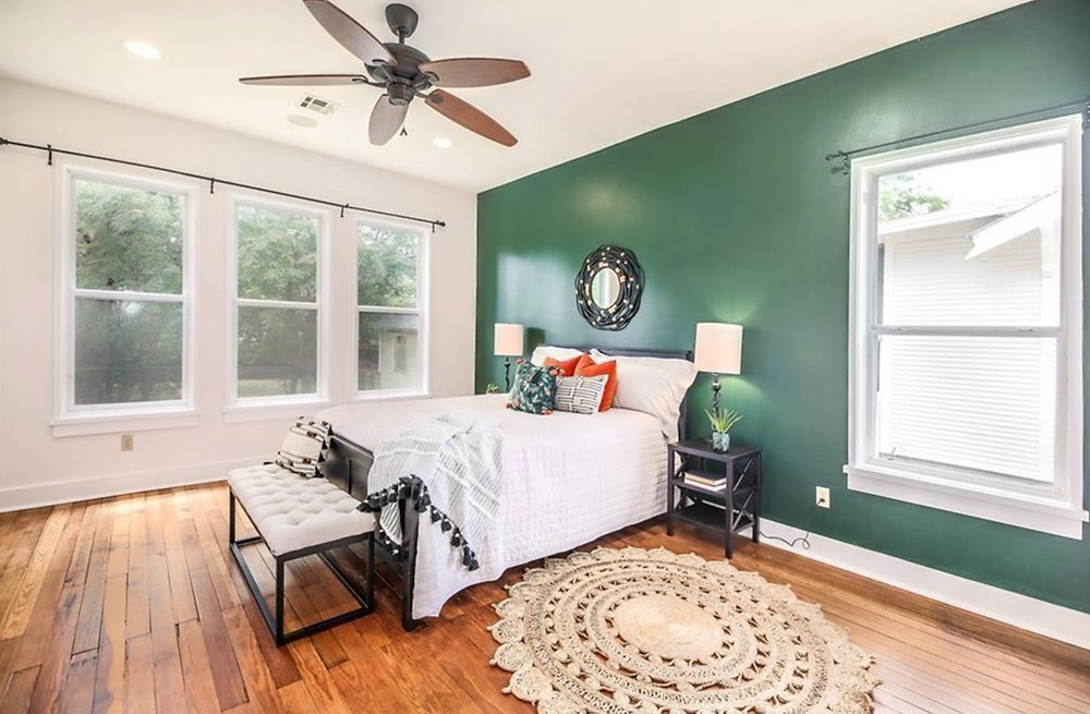 Bright and sunny bedroom with deep green statement wall, white bedding, and a round boho rug.