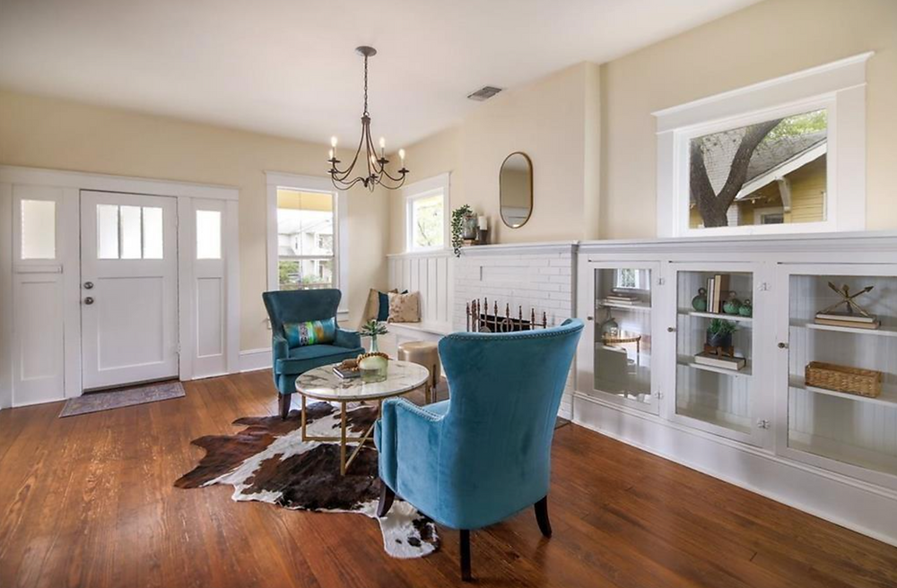 A charming home's front sitting room. Blue statement chairs at a faux marble table, with a brown and white cow skin rug in front of bright white built in cabinets and a fireplace