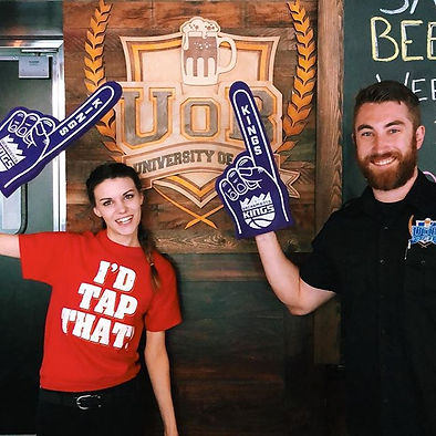 Two employees pointing at a UOB logo