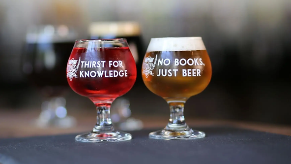 """Two beers. One beer with text """"Thirst for knowledge"""". The other beer with text """"No books, just beer""""."""