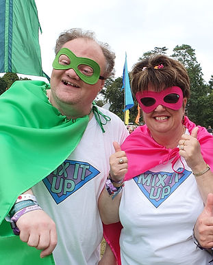 "2 members at a festival. 1 male, wearing a green supergero cape and mask and a t-shirt with ""Mix It Up"" written on it. He is putting his right arm out in a superhero pose. 1 female wearing a pink superhero cape and mask, also wearing a t-shirt saying Mix It Up. She has her thumbs up."