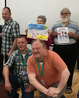 An image from a speaking up group. 2 members of staff are knelt down infront of 3 other people. The 2 members of staff are male and are both smiling. There are 3 people on the back row. the first is a male looking at the camera. the second is a lady holding up a picture she has made and the thirs is a male holding up an easy read document