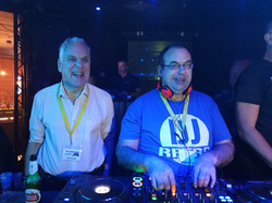 2 male DJs with learning disabilities wearing yellow lanyards