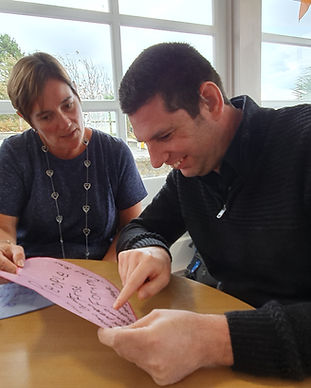 There is an image of a man and a woman looking at a piece of paper. the woman is supporting the man to read the information.