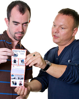 2 men holding and looking at a Keeping Safe Card