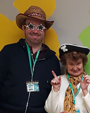 2 members wearing fancy dress. 1 male member is smiling and wearing glasses in the shape of stars and a cowboy hat. The lady is also smiling and wearing a pirates hat.