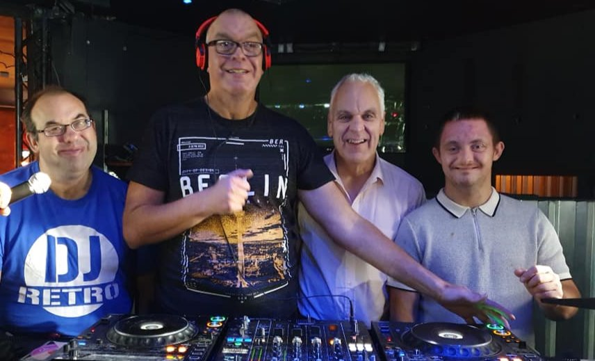 4 male DJs with learning disabilities looking at the camera from behind DJ decks