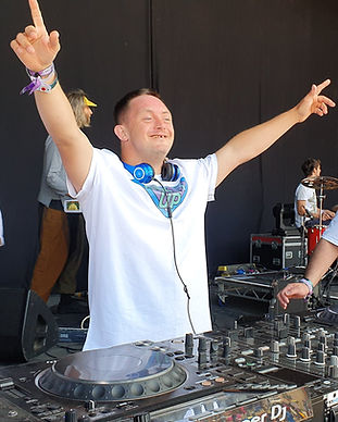 "a male member wearing a white tshirt with the words ""mix it up"" in a superhero style logo. He is standing behind some dj decks and has blue headphones around his neck. He is smiling and holding both his arms out in the air."