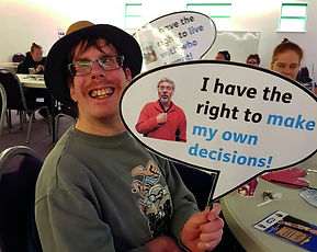 "A button that links to our about us page. There is a man wearing glasses and a hat, smiling at the camera and holding up a sign that says ""i have the right to make my own decisions"""