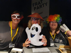 3 women volunteering at the club night, all wearing funny costume props including a mask, hat and co