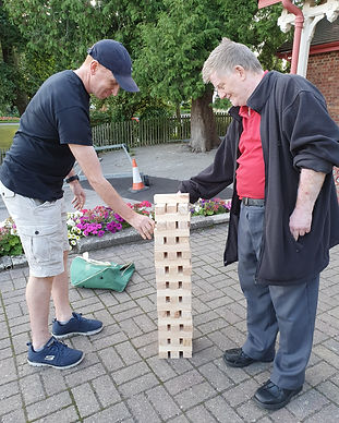 2 male memebers playing giant jenga outside