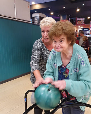 An image of 2 women at a bowling alley. one woman is looking ahead and concentrating on pushing the ball down the ramp. the other lady is smiling and stood behind the first lady ready to support her if needed.