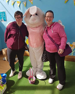 2 women standing either side of someone in a bunny costume with an easter basket on the floor in front at an Easter Fun Day