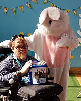 1 male member who uses a wheelchair with a donation bucket on his lap.  Next to him is someone in a bunny costume.  They are volunteering at an easter fun day