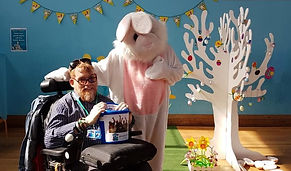 a button that takes you to the get involved page. an image of a man using a wheelchair holding a donation bucket on his lap. there is a person dressed as an Easter bunny stood next to him.